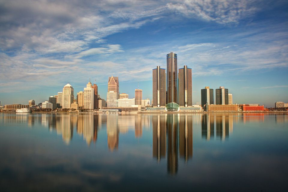 Detroit city reflection in river with cloudy sky.