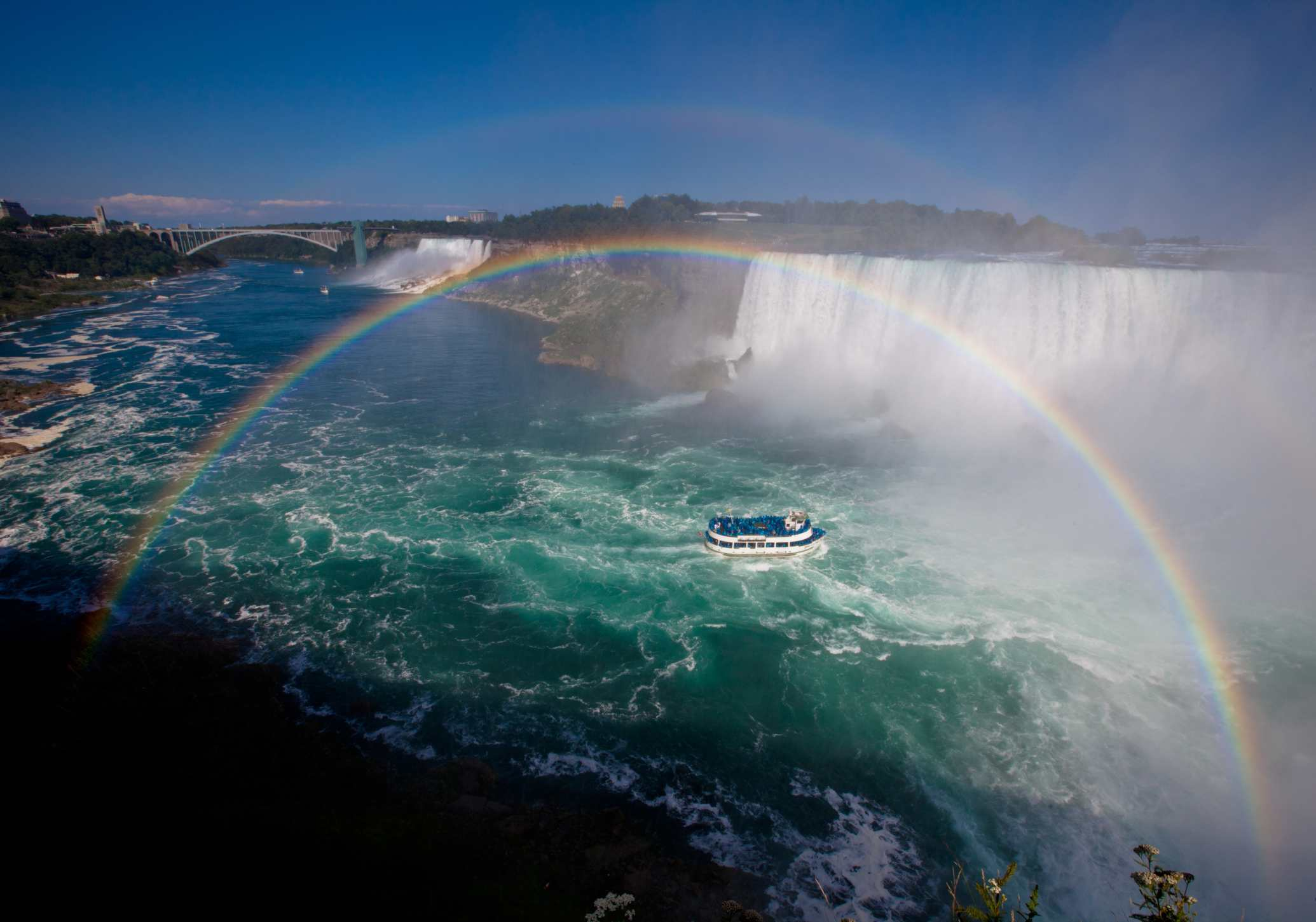 Niagara Falls with rainbow and Hornblower Boat Cruise.
