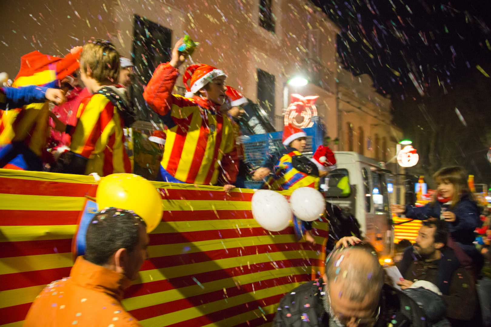 Children throw candy at the Three Kings celebration in Barcelona, Spain