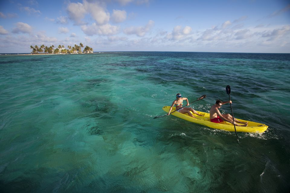couple kayaking with small tropical Island