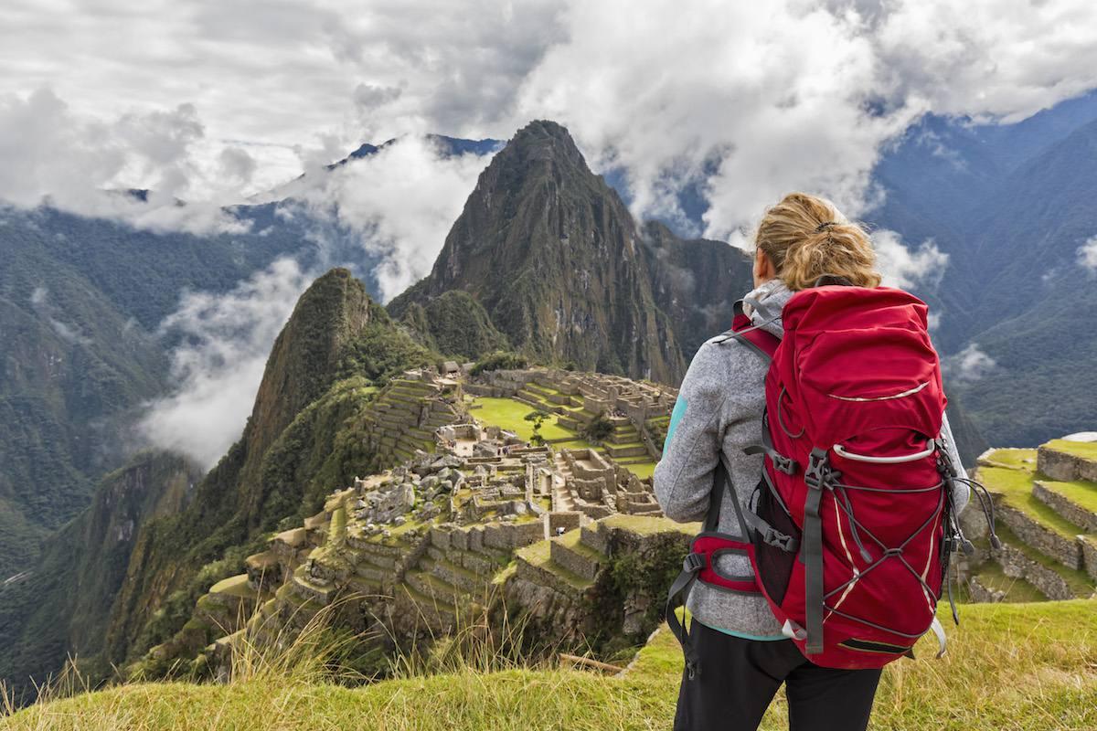 Tourist wearing red backpack on Machu Picchu