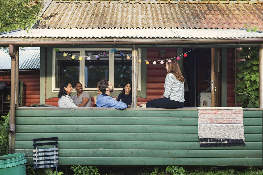 Happy friends enjoying party in log cabin