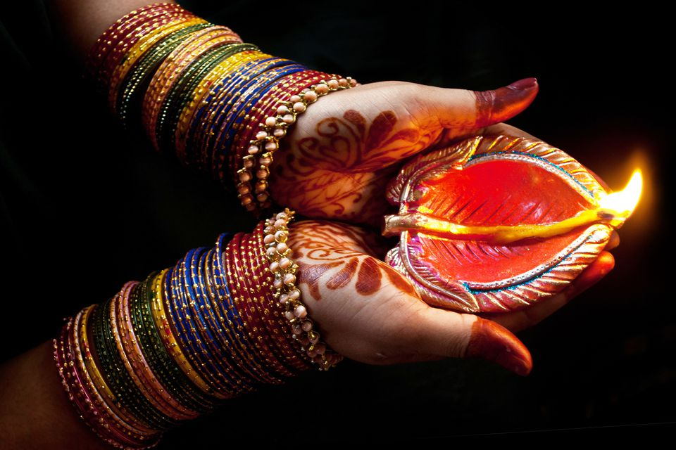 Woman with lit earthen lamp at Diwali festival