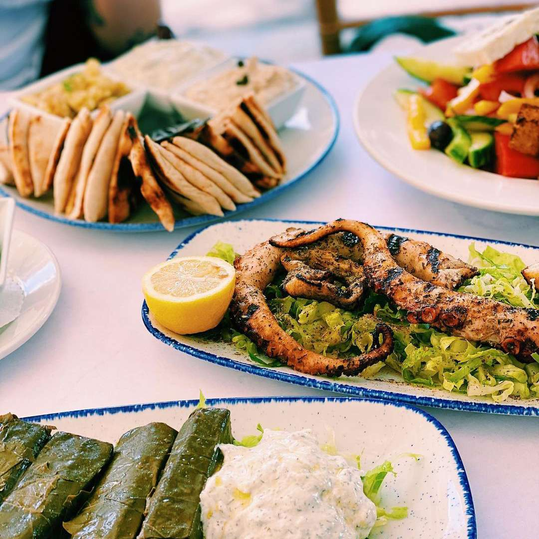Table with greek appetizers on it like octopus, pita, and hummus