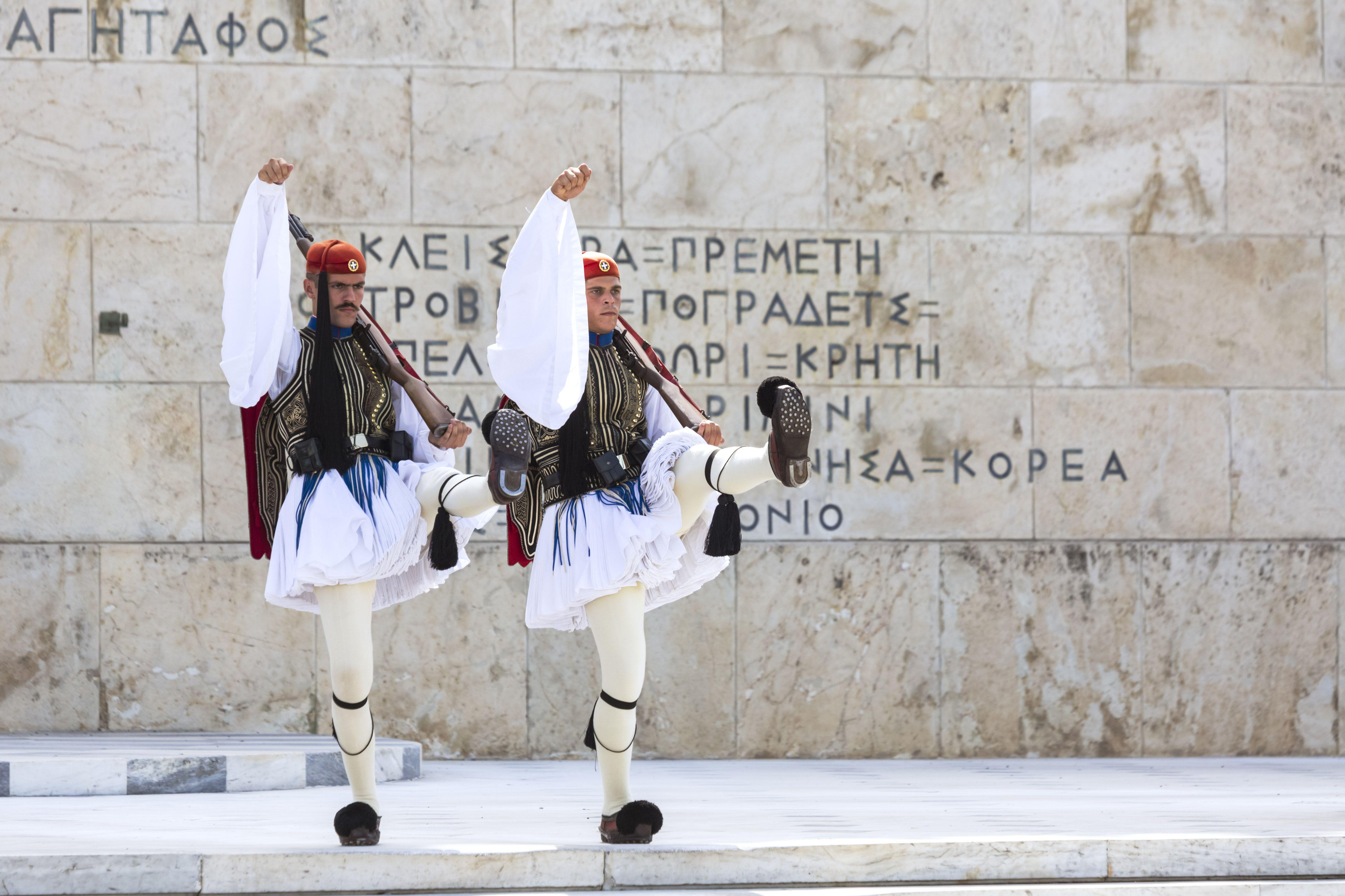 Grecia, Atenas, soldados con ropa tradicional caminando en la plaza Syntagma