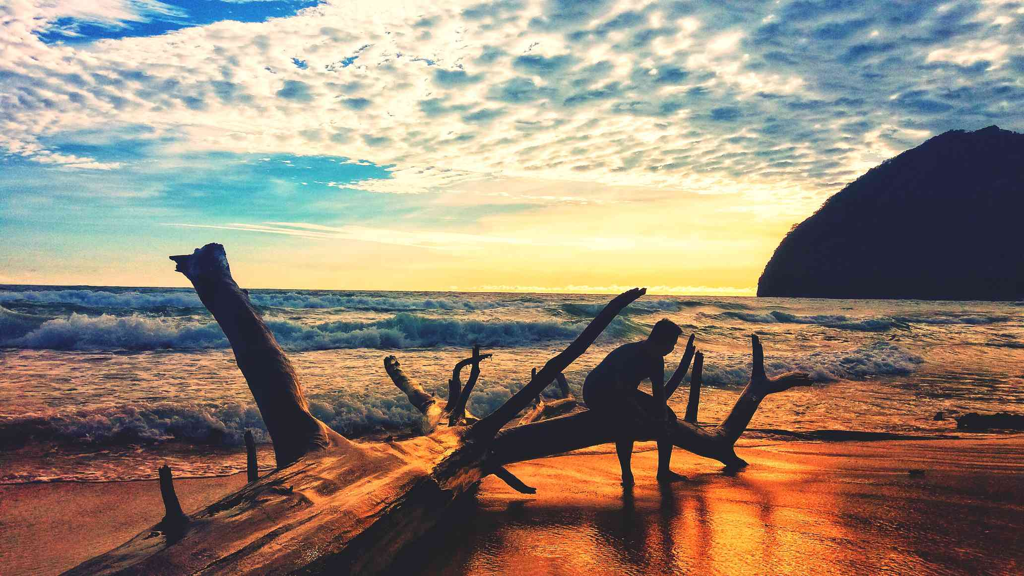 Silhouette Man Sitting On Driftwood At Lampuuk Beach