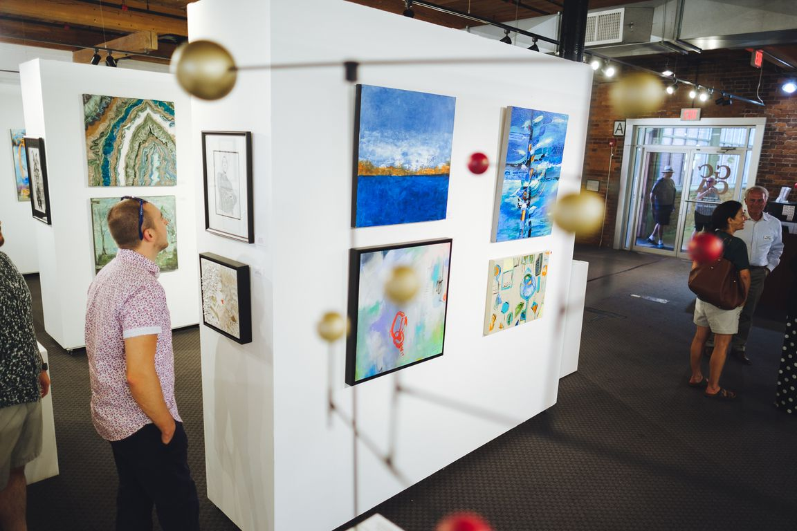 Man looking intently at a piece of art on display in a gallery