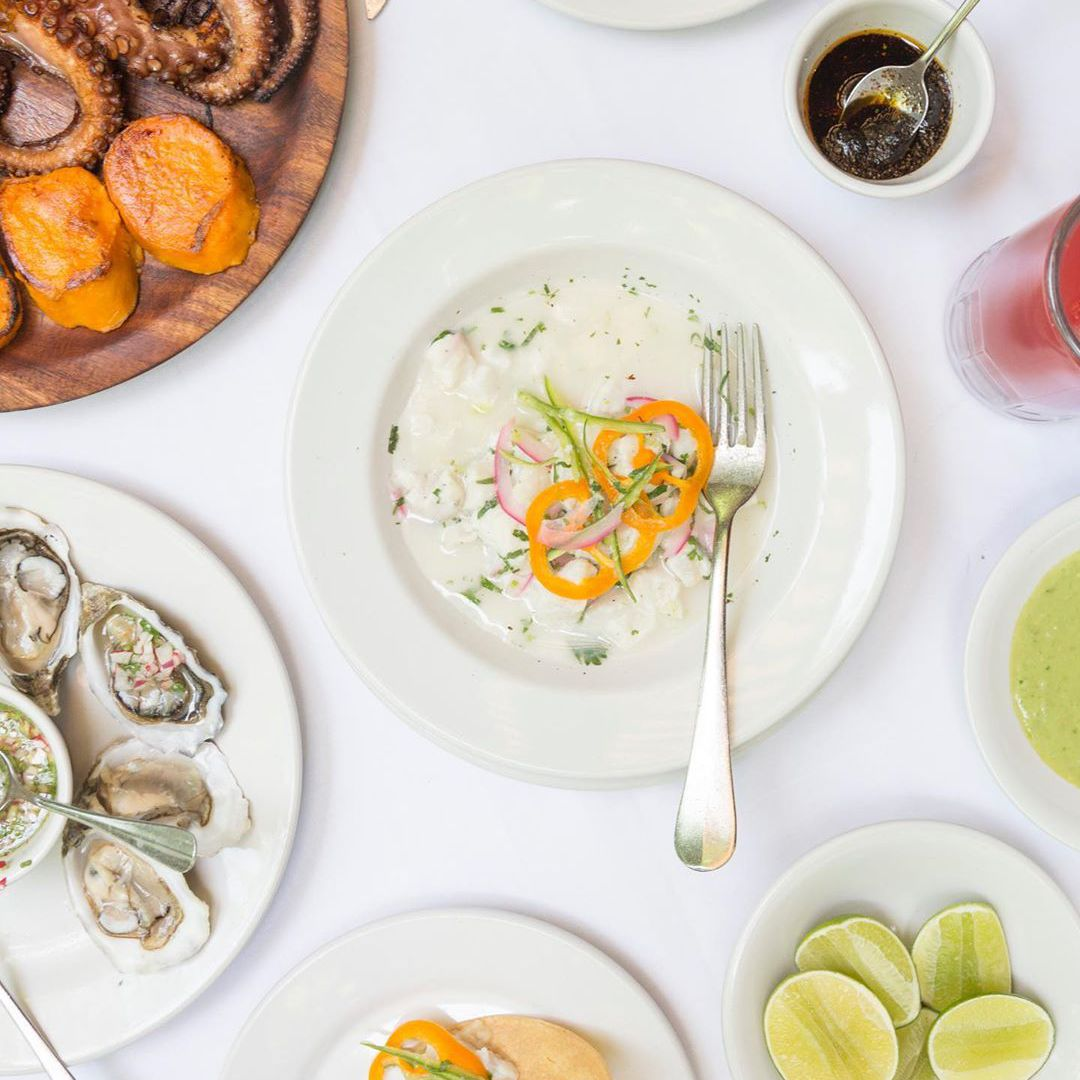 overhead photography of a creamy ceviche garnished with orange peppers from Contramar in mexico city. There is a fork in the shallow ceviche bowl. There is also a plate of limes on the table as well as oysters and a whole roasted octopus