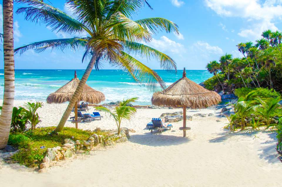 Beach at Tulum with straw umbrellas and palm trees