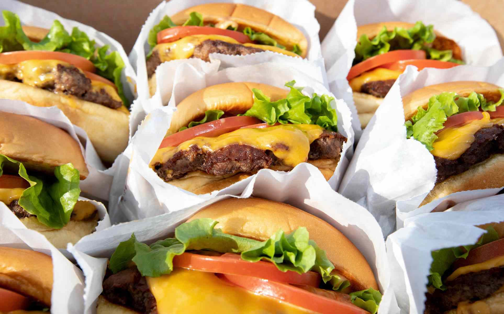 9 cheesburgers with lettuce and tomato in white paper bags