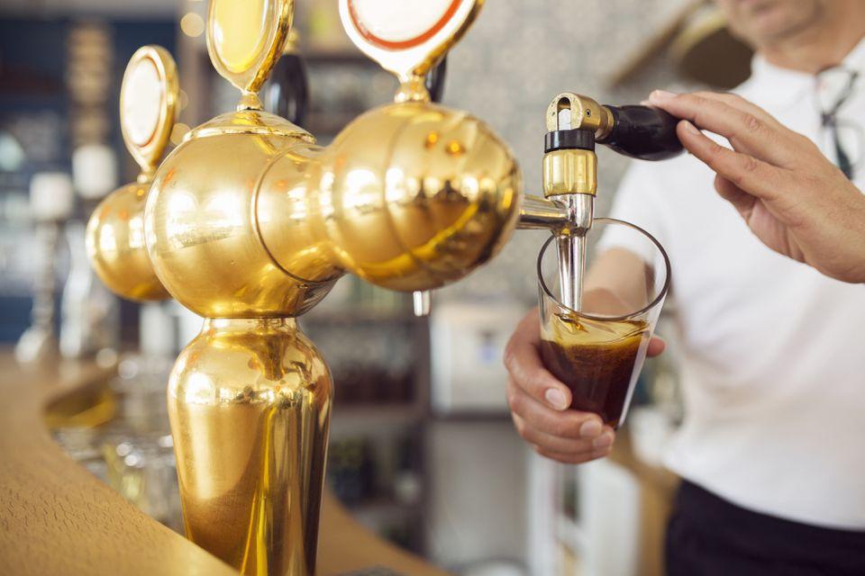Camarero vertiendo cerveza en vaso de cerveza