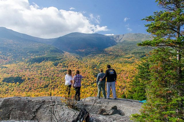 A family standing on a rock overlooking a valley of colorful trees during fall