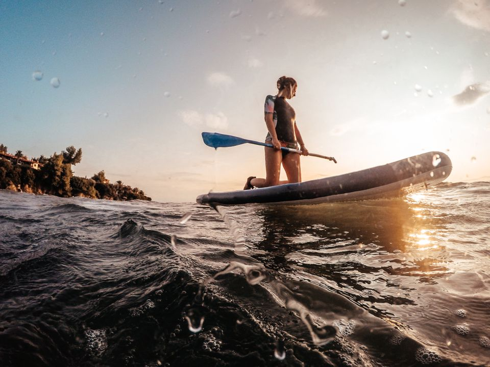 Young woman kneeling on a paddle board