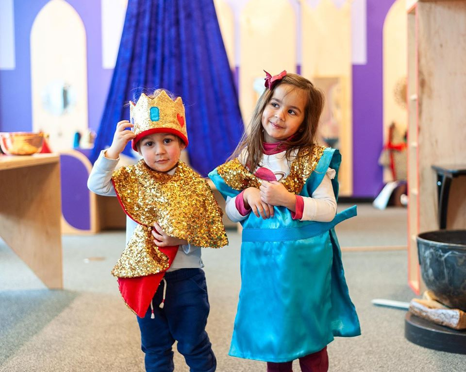 Two young children dressed like like a king and queen