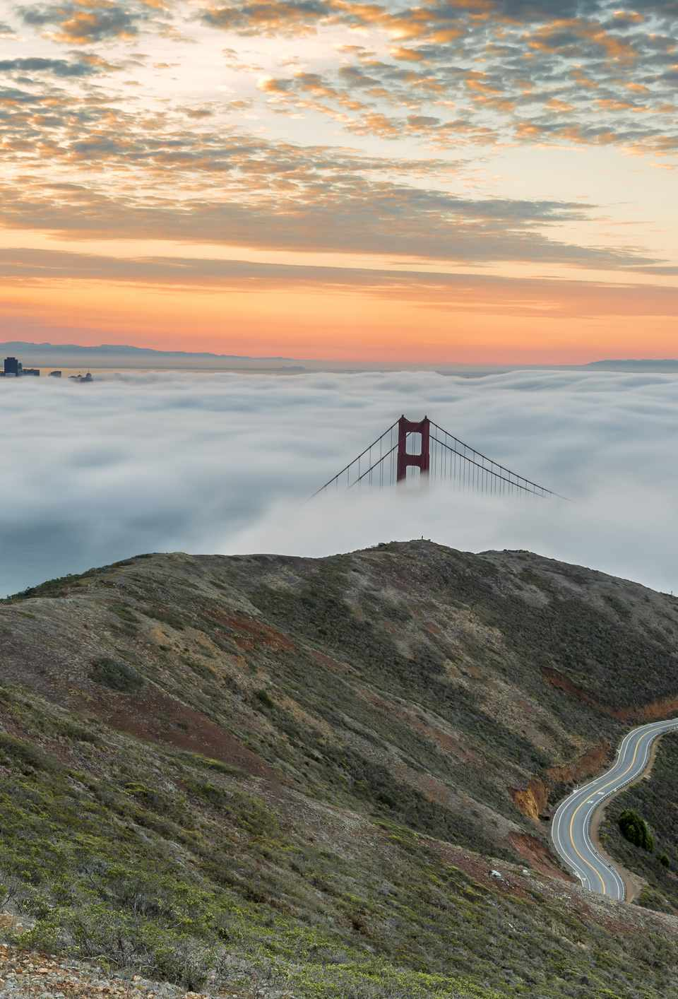 The towers of the Golden Gate Bridge, just visible over a bank of fog