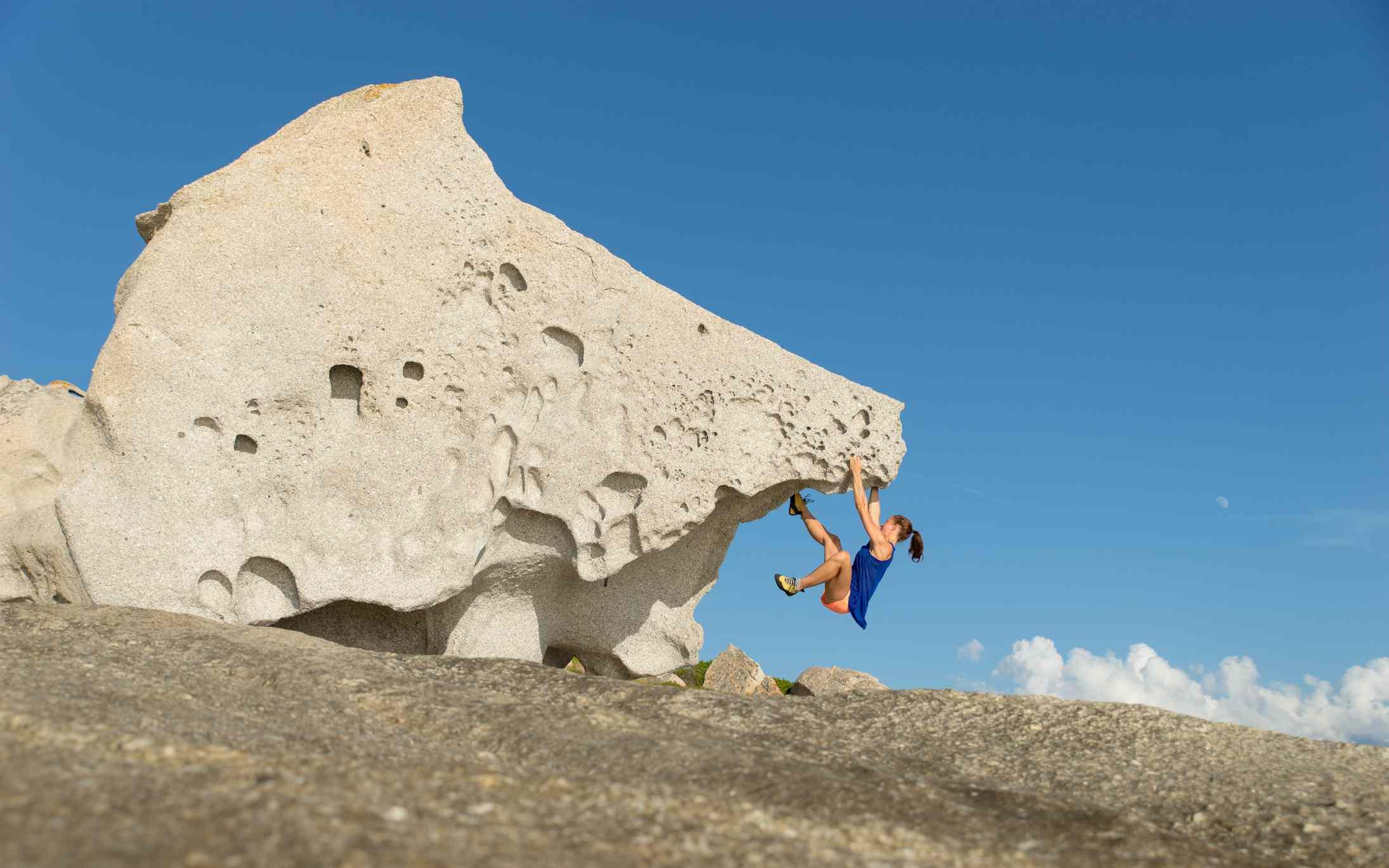 France, Corsica, Woman climbing on big single rock