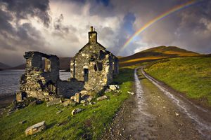 Derelict house by remote loch, dramatic skies and rainbow