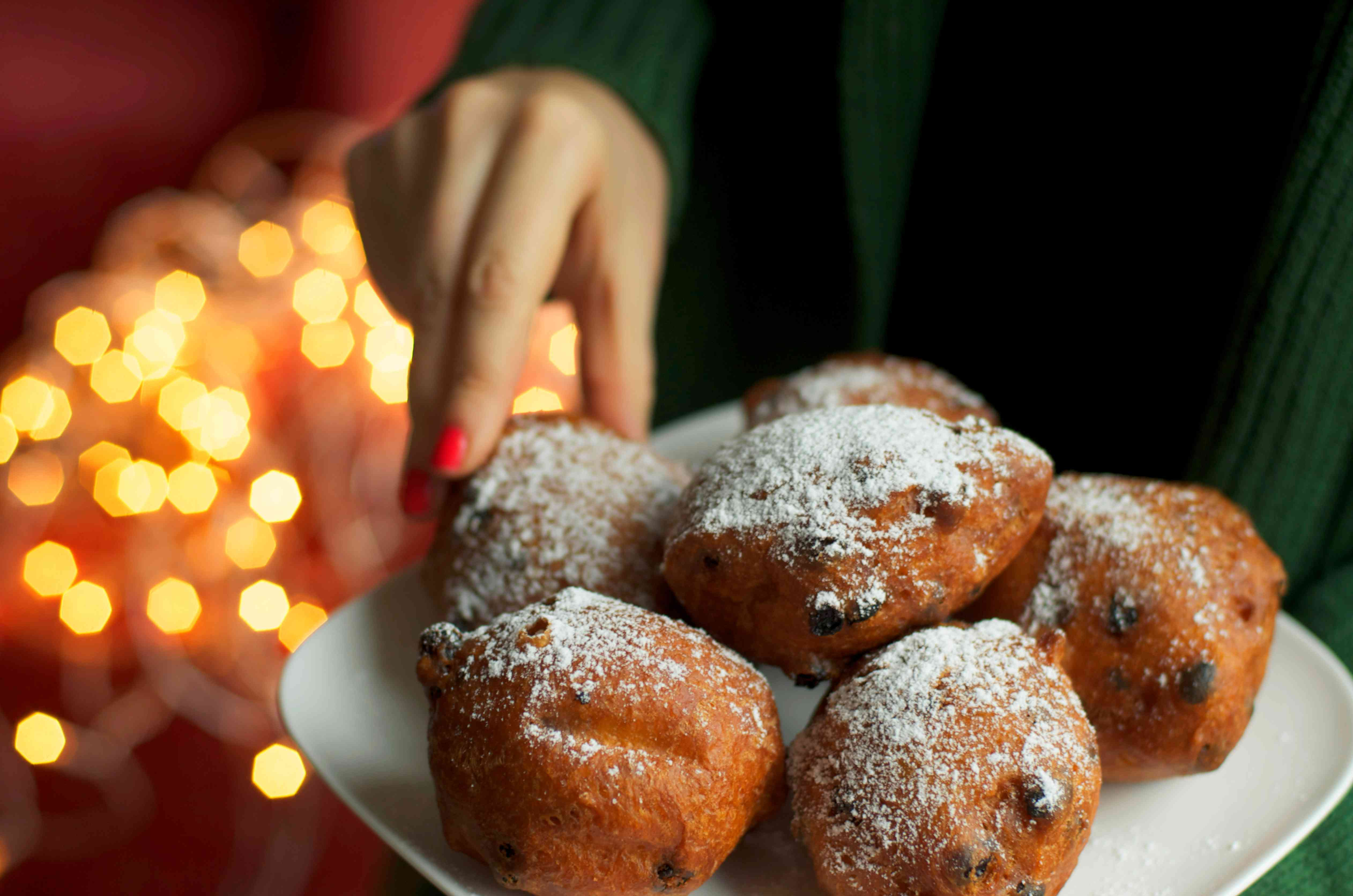 Traditional dutch oliebollen donuts oliebollen. A woman picking one donut, bokeh lights background