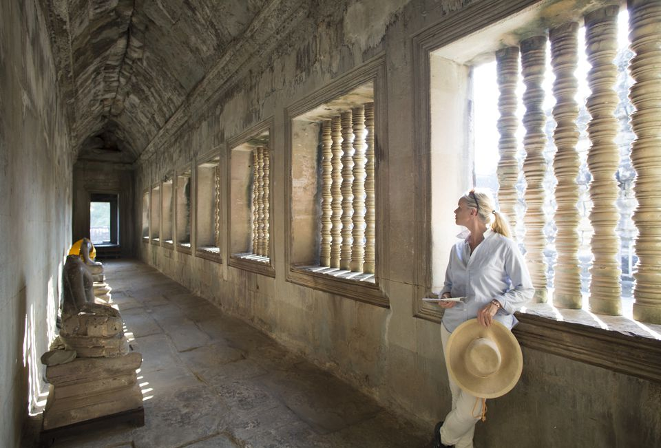 Woman pauses in Angkor Wat hallway, Cambodia