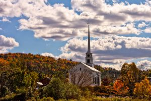 White church with a tall steeple in Stowe, Vermont with the trees in full fall color