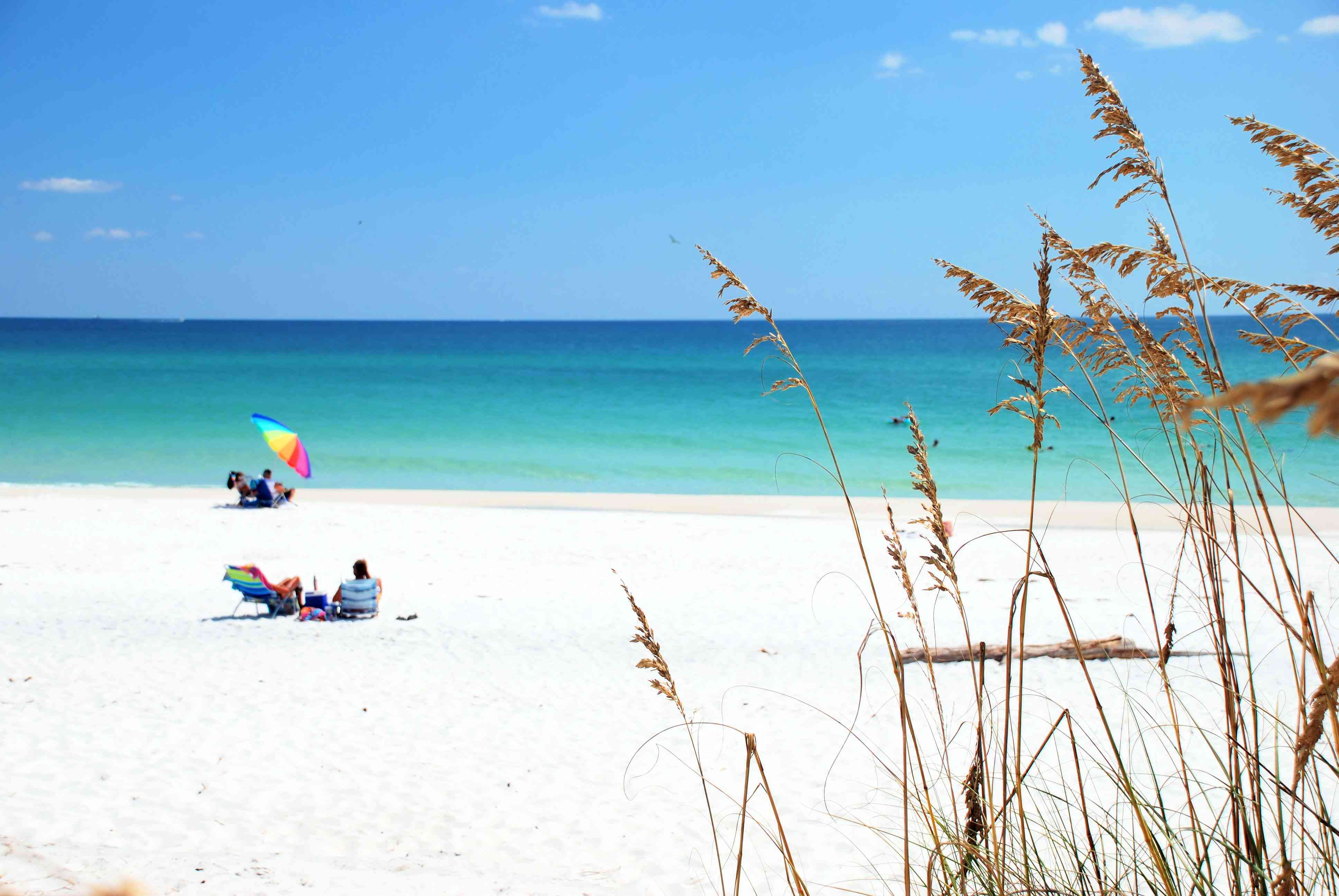 Beach goers enjoying white sand and emerald water of Destin, Florida