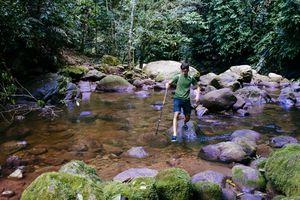 Young boy is crossing an clear river in the tropical rain forest near Tarapoto/ San Martin/ north peru/ South America