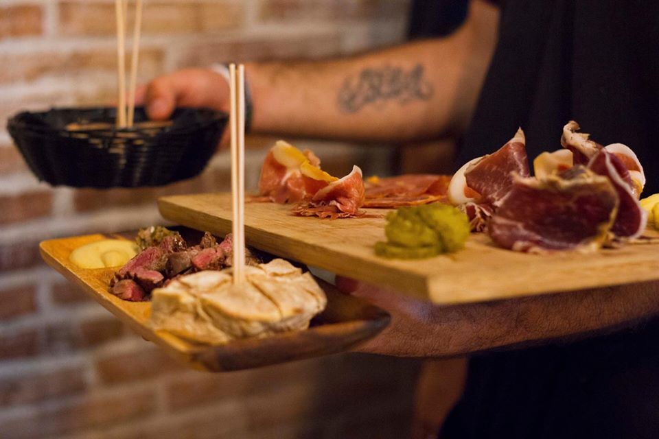 Waiter holding a basket and a charcuterie board