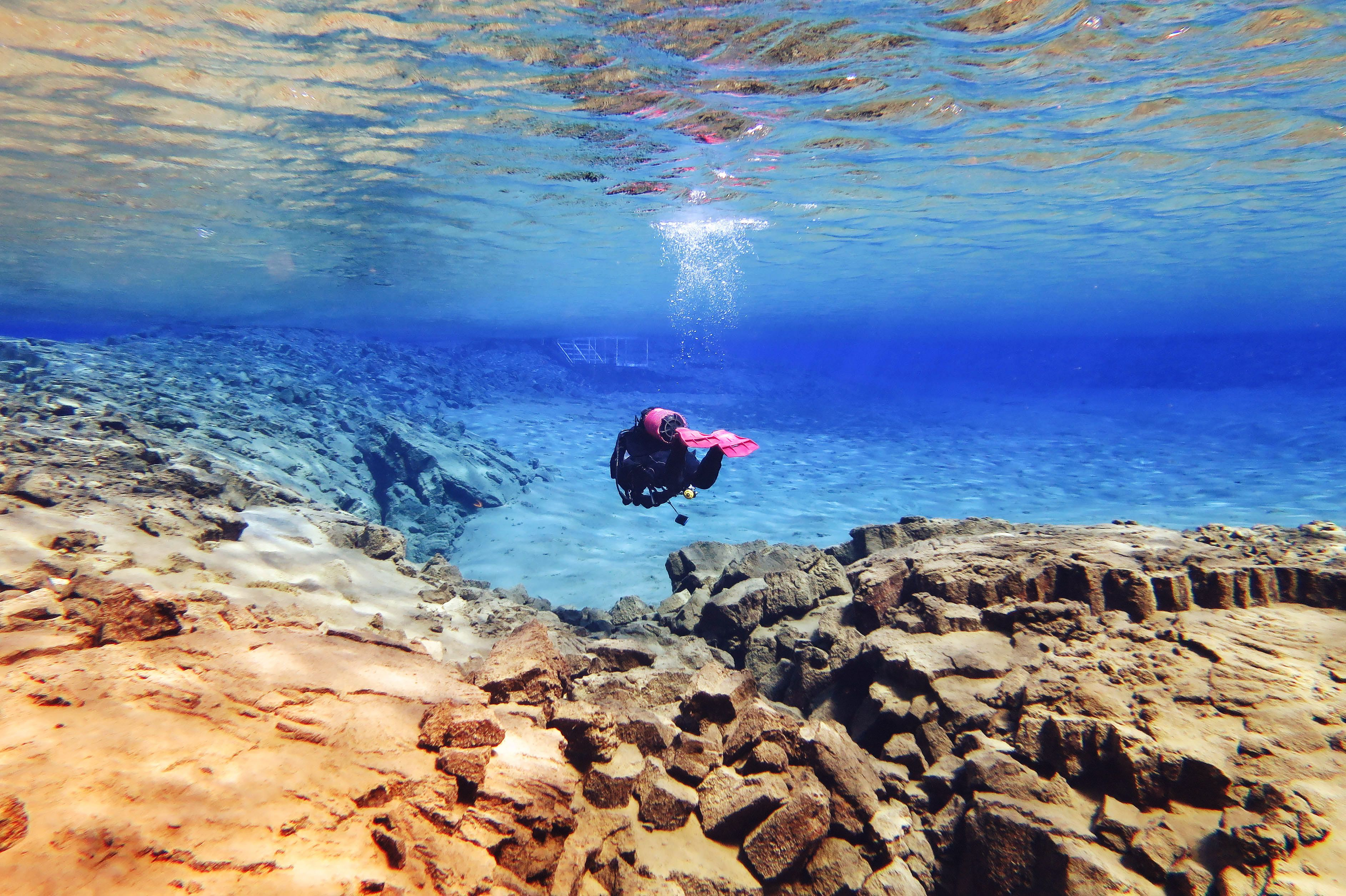 a scuba diver in the waters at silfra