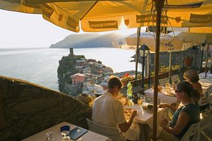 People dining in an outdoor restaurant with a view of the sea, Vernazza, Italy