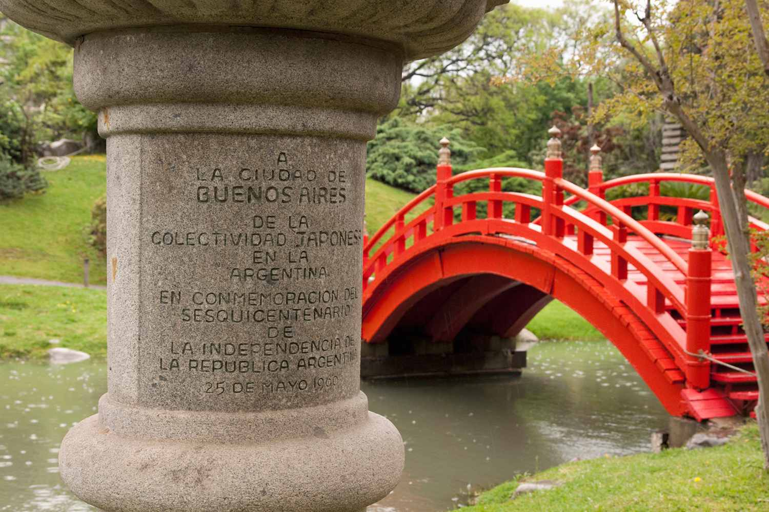 An inscription on a post with a red bridge in the background at the Japanese Garden in Buenos Aires