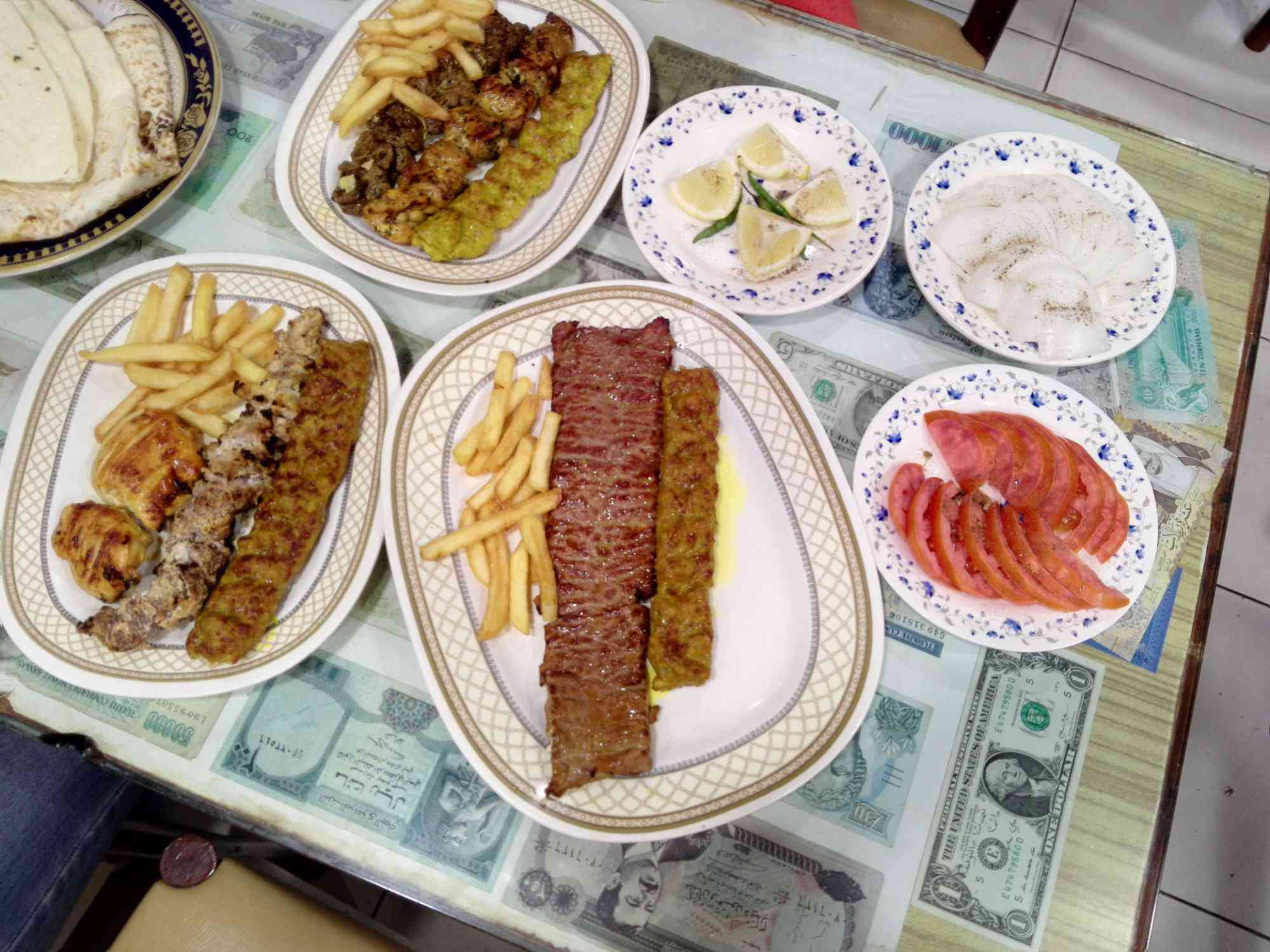 plates of various grilled meats served with french fries on a table with sliced tomateos, slice onions, and lemon wedges. The table has various currencies on it, sealed under a protective layer