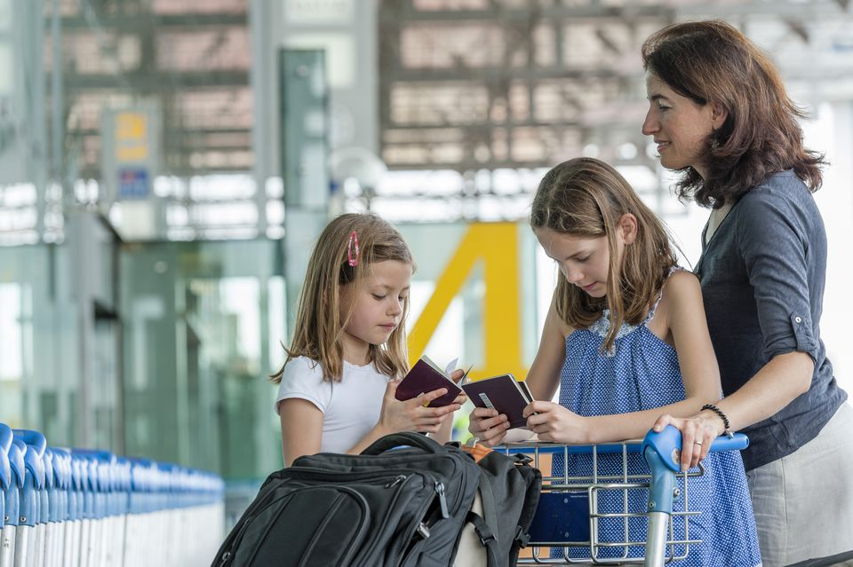 Mother and daughters standing outside of airport with luggage