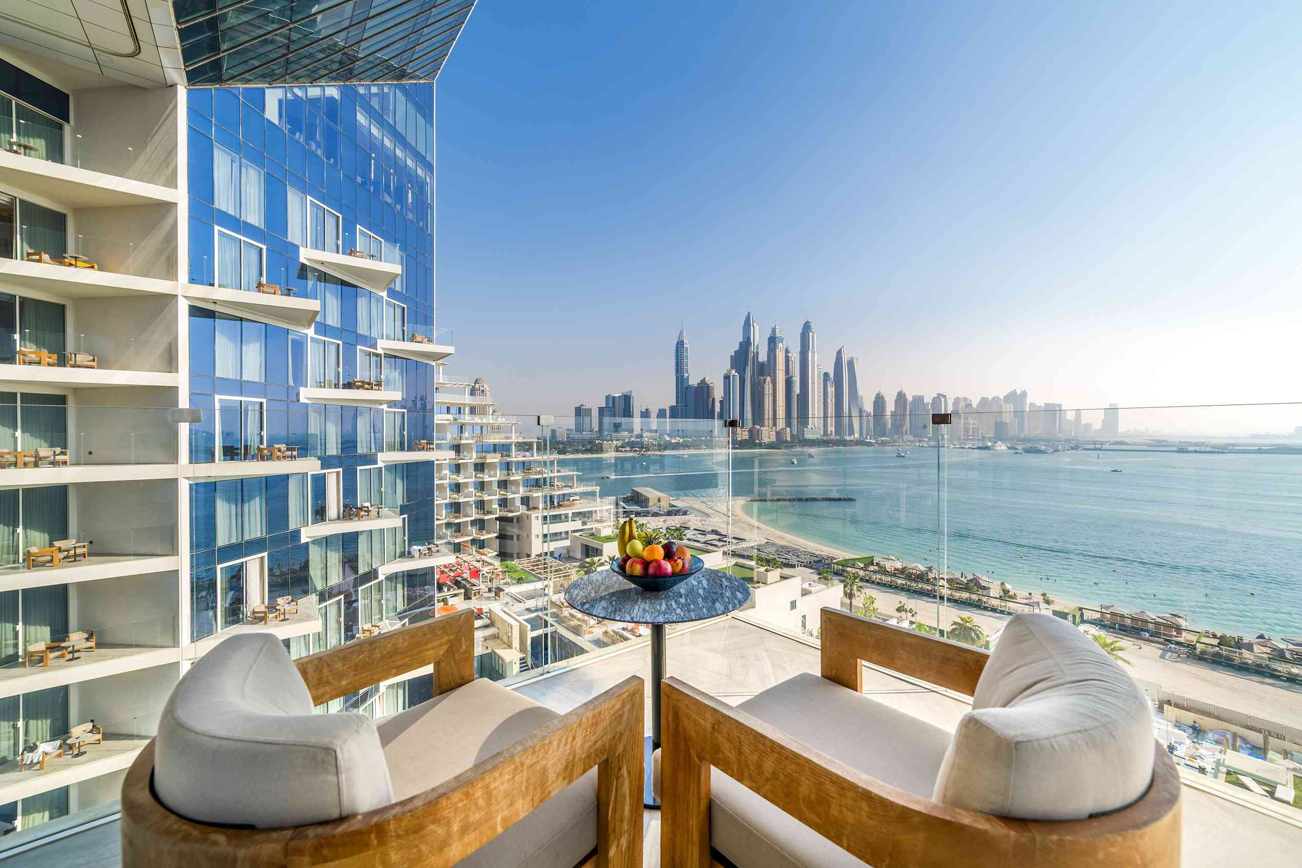 two chairs on an outdoor patio with the ocean and Dubai skyline in the distance