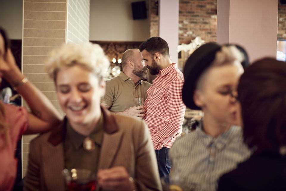 Gay and lesbian couples intermingling at a bar.