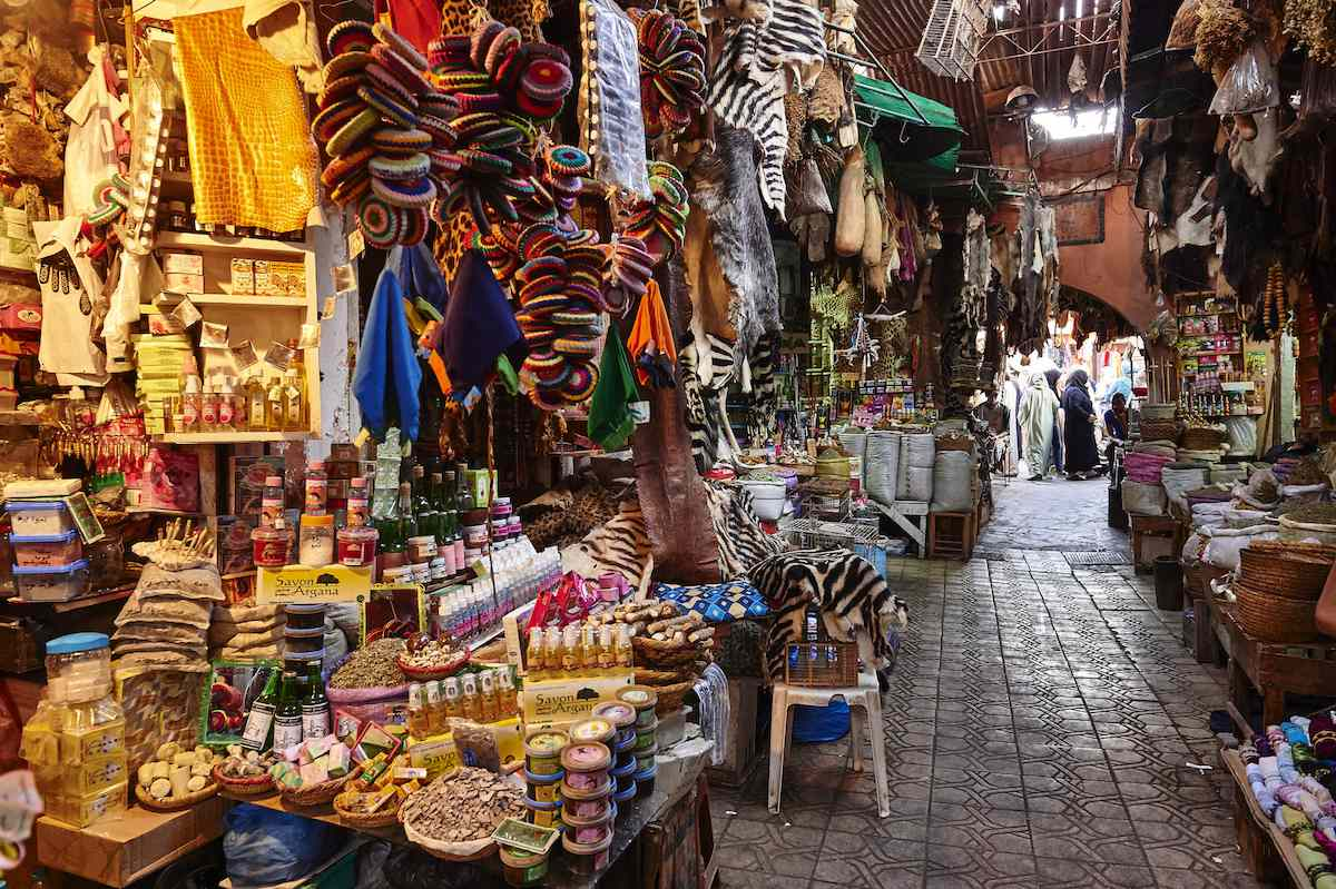 A colorful marketplace lines a narrow alleyway in Morocco