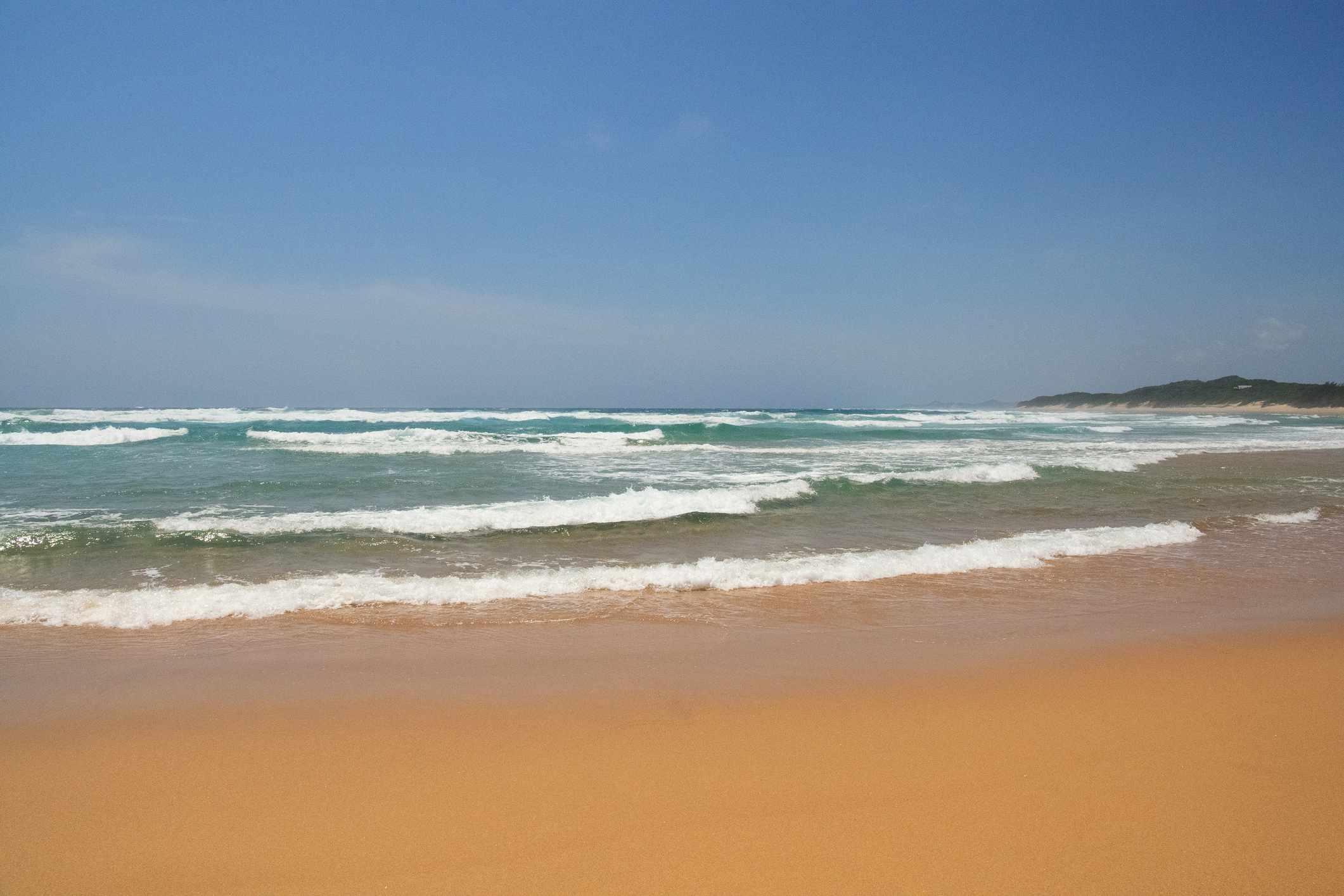 small waves crashing on a golden sand beach