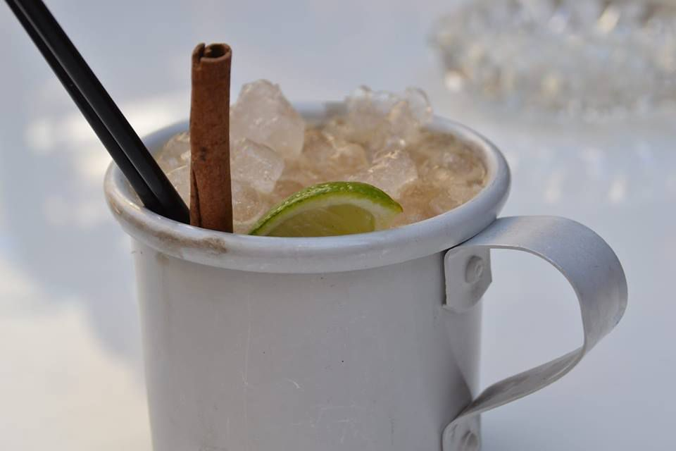 Cocktail from The Art Foundation in Athens in a White metal mug with a cinnamon stick and slice of lime with two black straws