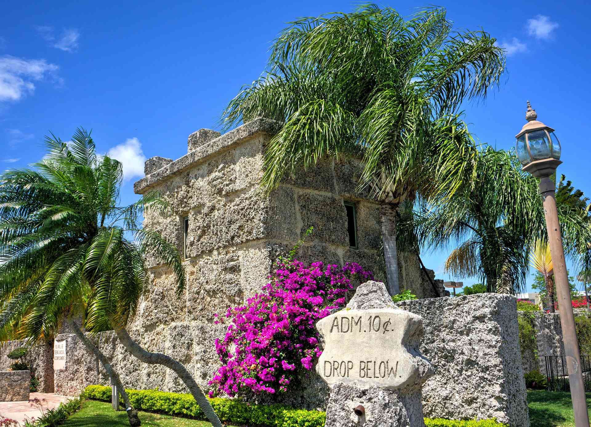 Coral Castle entrance with trees and flowers