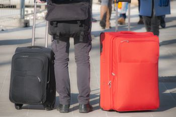 9630725d73b8d4 Should You Take a Backpack or Duffel on Your Next Trip  Man takes a rest in  between two suitcases