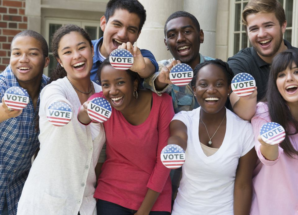 "young people holding up buttons that say ""vote"""