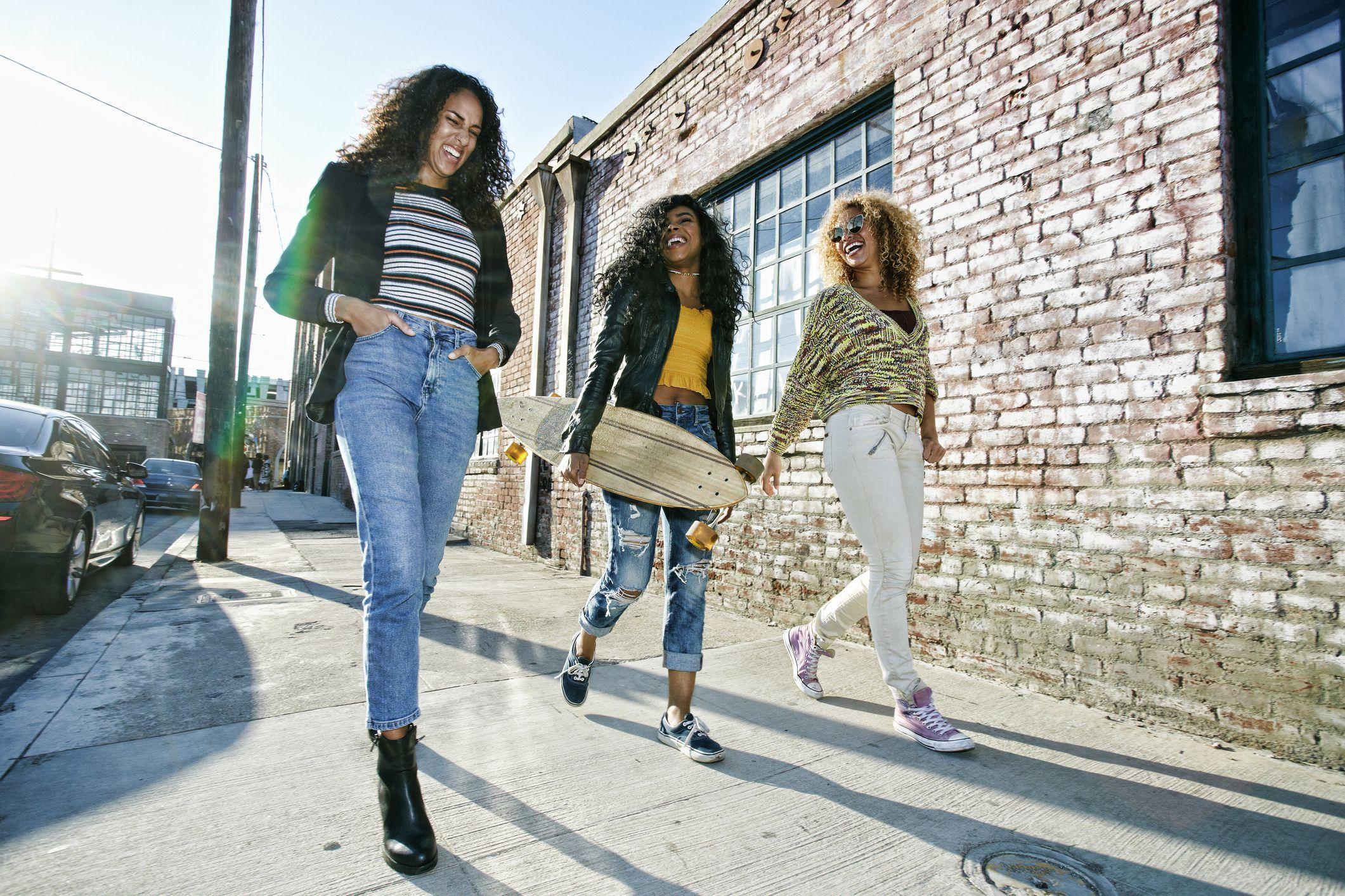 Three young women in LA walking along pavement, one carrying skateboard