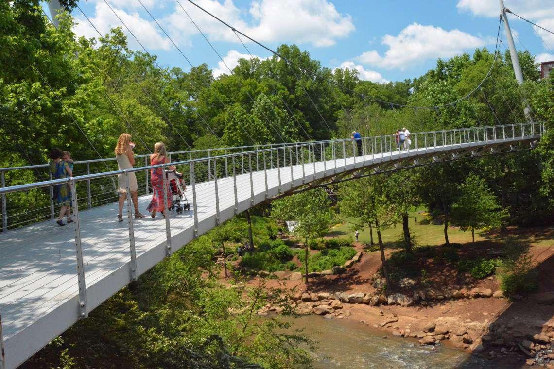people walking on a suspension foot bridge over a creek