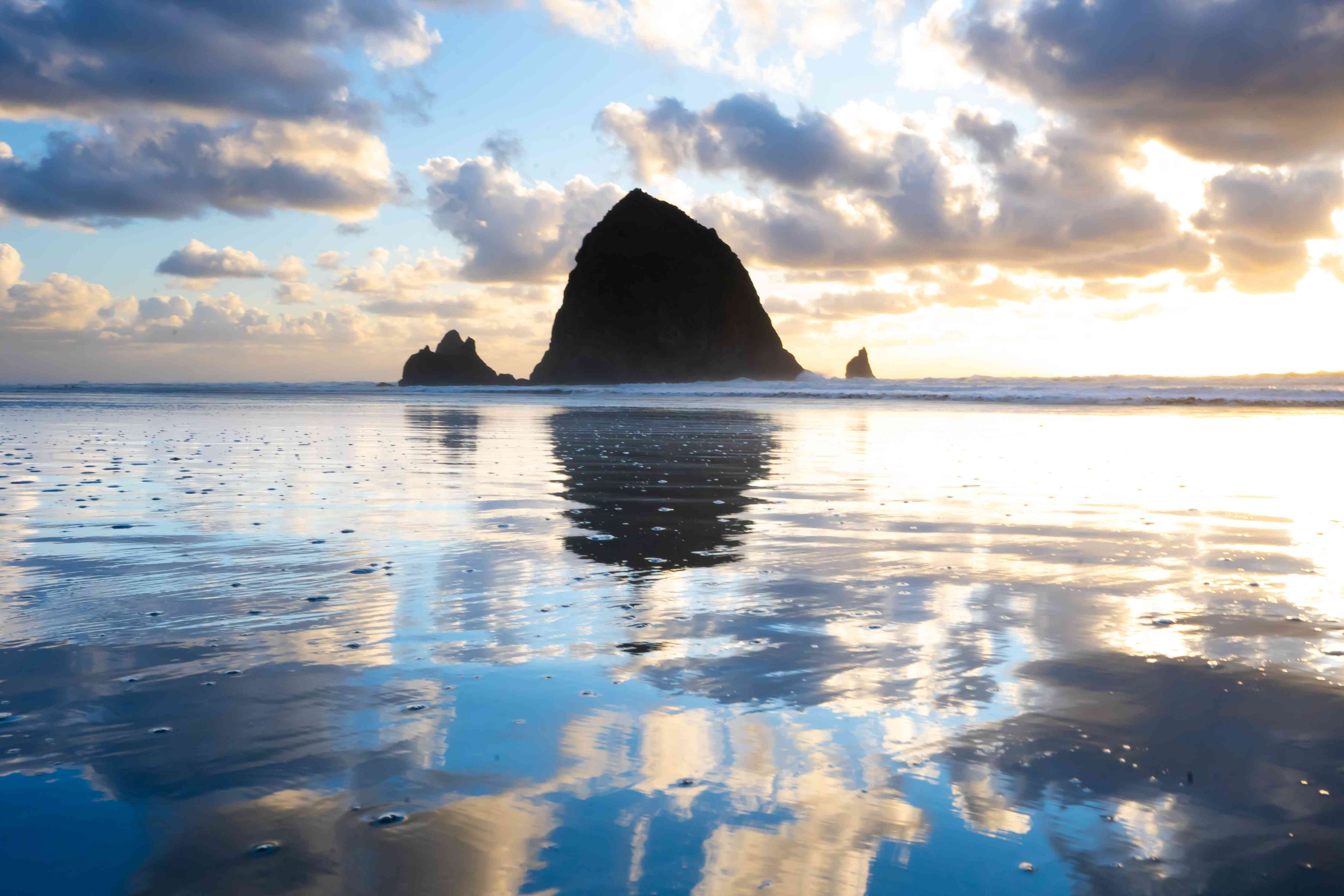 Haystack Rock reflected in the water during sunset