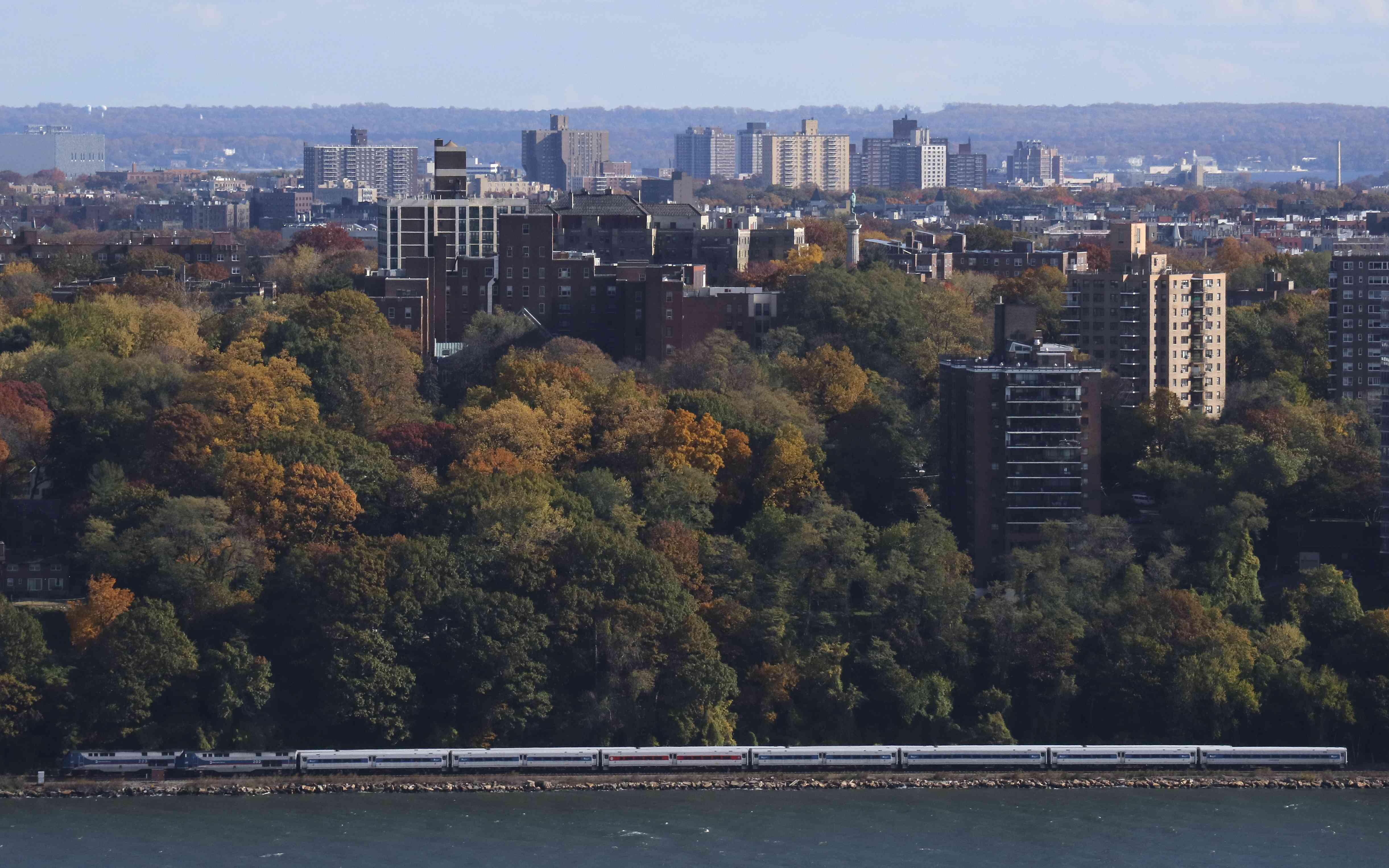 A Metro North train passes along the Hudson River in New Rochelle, NY...