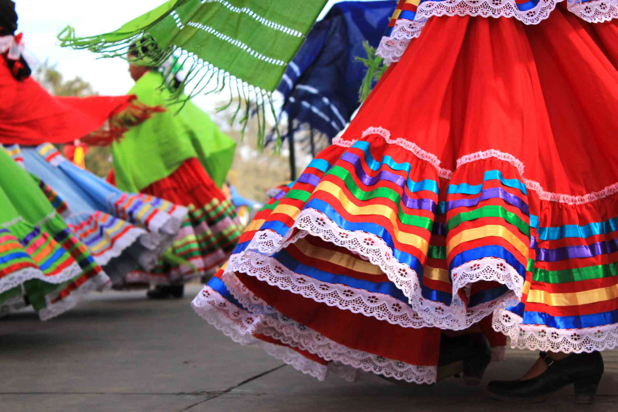 Close up of colorful skirts flying during traditional Mexican dancing. Young girls perform on a stage during an event celebrating Latino culture and heritage.