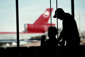 Attendant pushes a passenger who uses a wheelchair to a departure gate