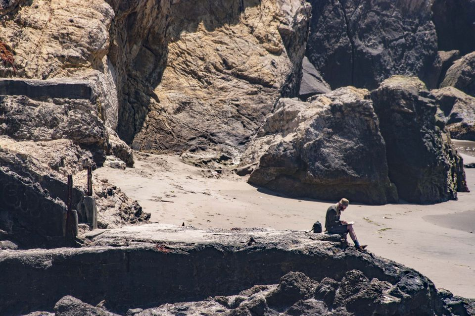 A man writing on a notebook sitting on rocky cliffs at Lands End