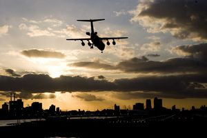 An airplane lands at an airport with Canary Wharf in the background