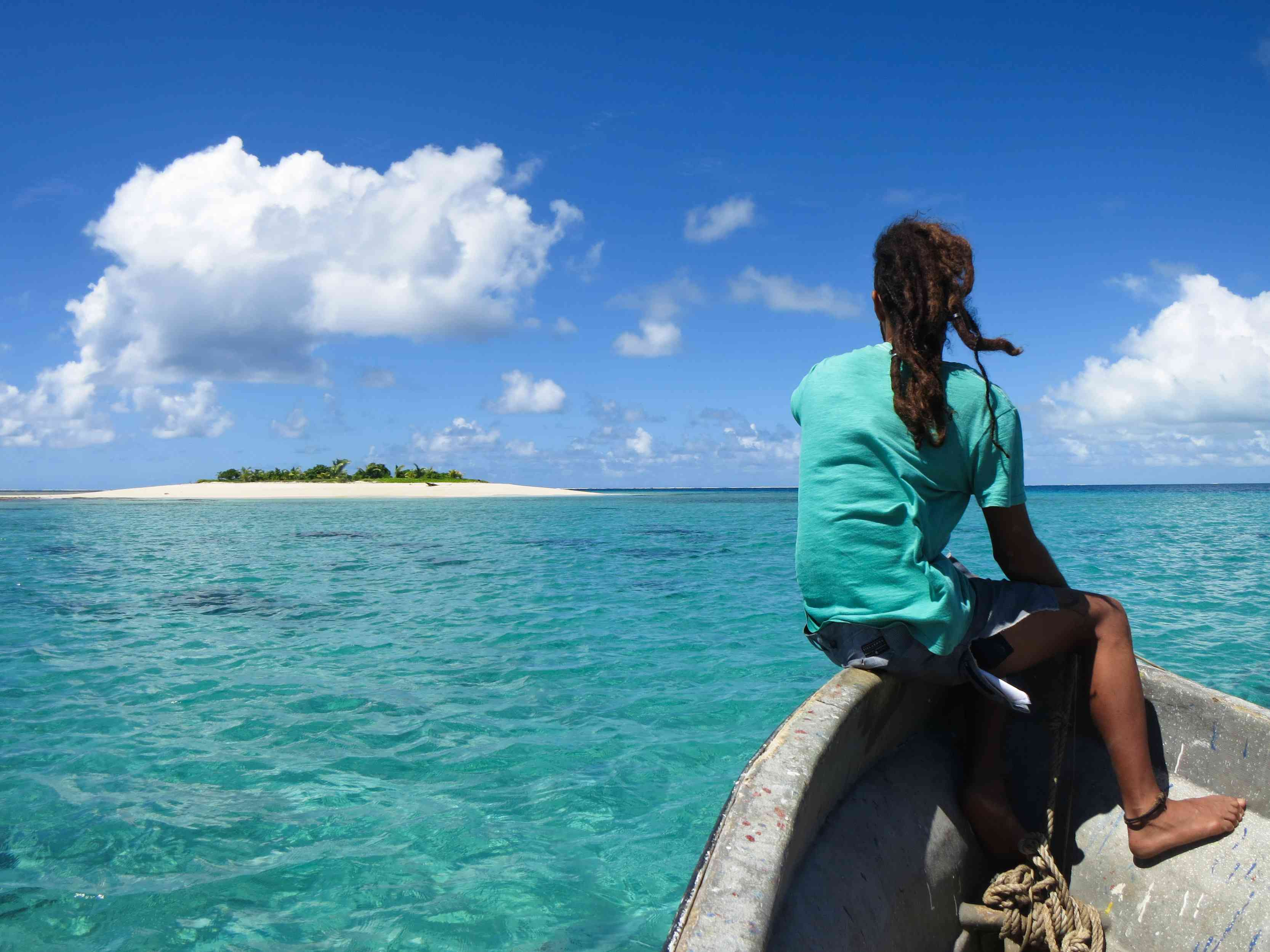 a person on a small motor boat headed towards Fiji