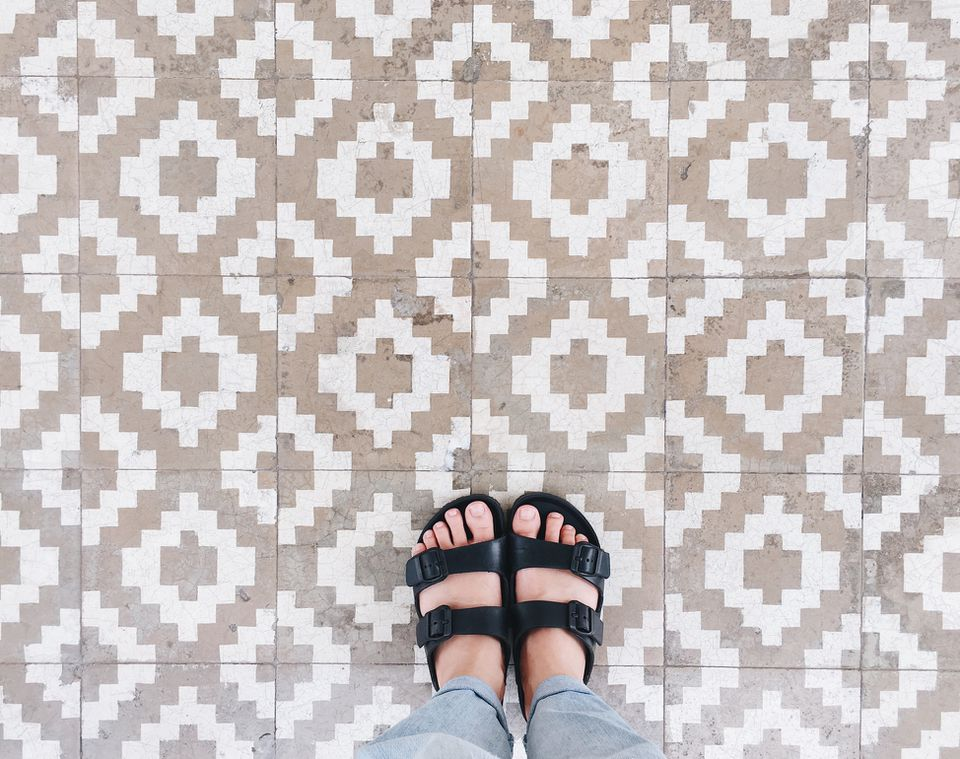 Person wearing sandals on tiled floor in Bangkok, Thailand